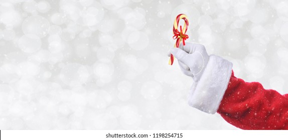 Santa Claus hand holding a candy cane over a silver bokeh background with snow effect. Banner size with copy space.