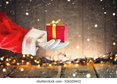 Santa Claus hand holding Christmas Gift box over wooden background. Proposing product. Advertisement gesture presenting point. Decorated Christmas tree with Winter Holiday Gifts