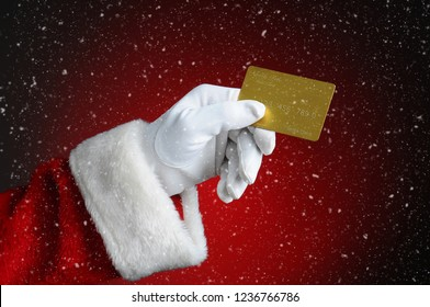 Santa Claus hand holding a gold credit card over a light to dark red background. Holiday Shopping / Cyber Monday concept.