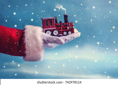 Santa Claus hand holding  train toy on winter background.
