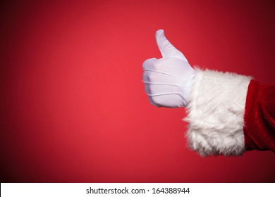 Santa Claus hand showing thumbs up ok sign over red background with copy space