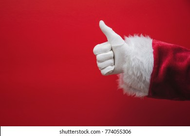 Santa Claus hand thumbs up against a red background