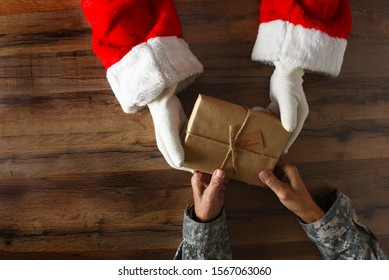 Santa Claus handing a plain wrapped Christmas Present to a soldier. High angle shot with only hands and arms visible.