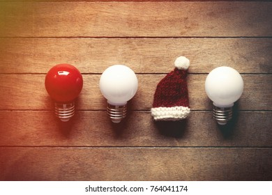 Santa Claus hat and bulbs on wooden background