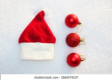 Santa Claus hat Christmas background with colored Christmas balls, Christmas toys, balls, decorations on a white snow background Merry Christmas theme of winter holidays. in the snow with gentle boke