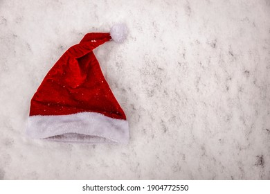 santa claus hat hanging forgotten in the snow