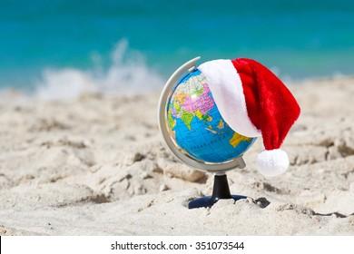 Santa Claus Hat on Globe at tropical beach. Christmas travel concept