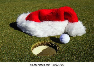 Santa Claus Hat on the Golf Course Next to Golf Ball and cup