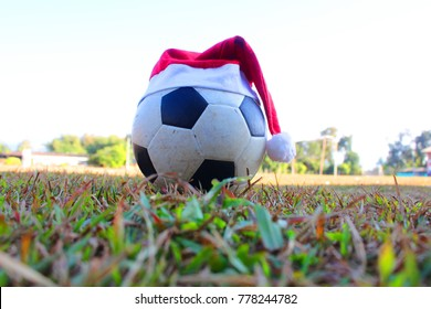 Santa Claus hat on the soccer ball. Merry Christmas in the Field Santa Claus red hat with old soccer ball on the lawn. merry christmas and happy new year 2018.Thailand