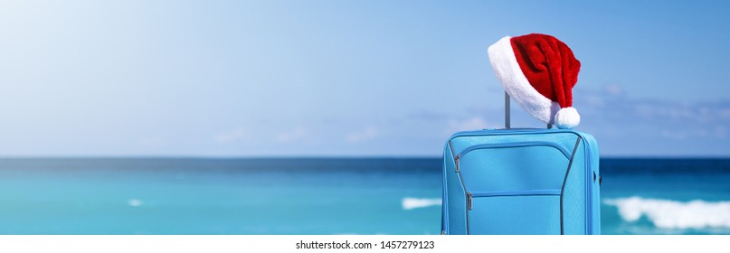 Santa Claus hat on suitcase handle with tropical beach and turquoise sea background. Christmas and New Year celebration. Nobody