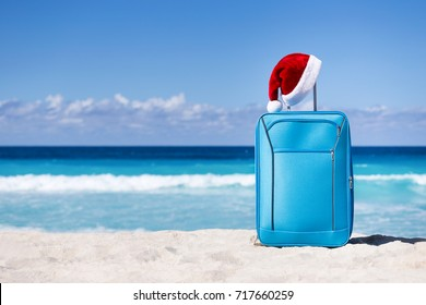 Santa Claus hat on suitcase handle with tropical beach and turquoise sea background. Christmas and New Year celebration. Nobody.
