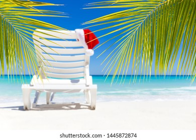 Santa Claus Hat on sunbed near  tropical calm beach with turquoise caribbean sea water and white sand. Christmas vacation. New year celebration. Travel destinations