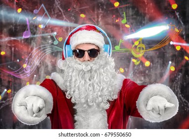 Santa Claus with headphones listening to music on blurred lights background. Christmas and New Year songs