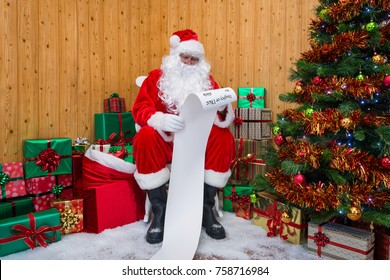 Santa Claus in his grotto surrounded by a Christmas tree with presents and gift wrapped boxes checking the Naughty or Nice list