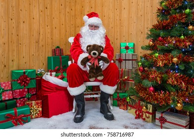 Santa Claus in his grotto surrounded by a Christmas tree with presents and gift wrapped boxes offering you a teddy bear.
