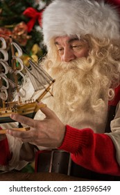 Santa Claus in his workshop making new toys for Christmas Presents for children around the world