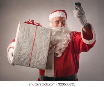 Santa Claus holding a big present and a smartphone