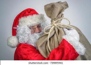 Santa Claus holding big sack full of christmas presents