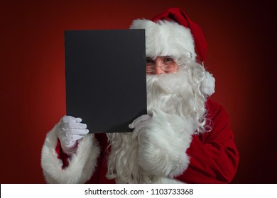 Santa Claus holding a black blank sign for custom message,