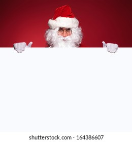 santa claus is holding a blank board on a red background