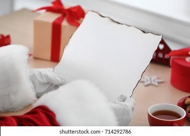 Santa Claus holding blank sheet of paper at table