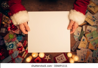 Santa Claus holding a blank sign, hands close up, top view, desktop with Christmas gifts and letters on background
