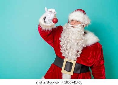Santa Claus holding a Christmas ornament isolated on mint colored background