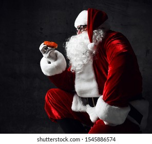 Santa Claus is holding delicacy red salmon caviar sandwich, looking at it going to eat on dark gray background. New year and Merry Christmas and happy holidays concept