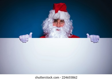 Santa Claus holding an empty board while looking at the camera, against blue background.