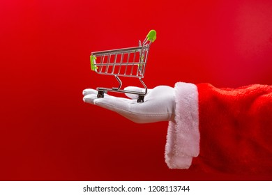 santa claus holding an empty shopping cart on hand