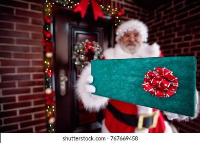 Santa Claus holding gift box, Santa Claus gloved hands holding big gift box.Santa Claus brought gifts for Christmas