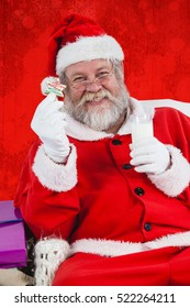 Santa claus holding glass of milk and star shape cookie against red paint splatter background