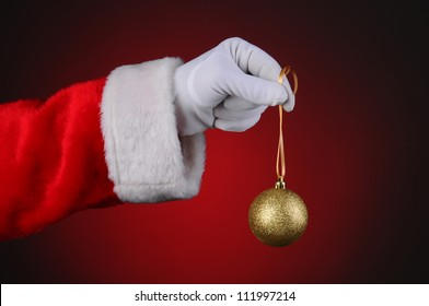 Santa Claus holding a gold sparkly tree ornament over a light to dark red background. Horizontal format showing only hand and arm.