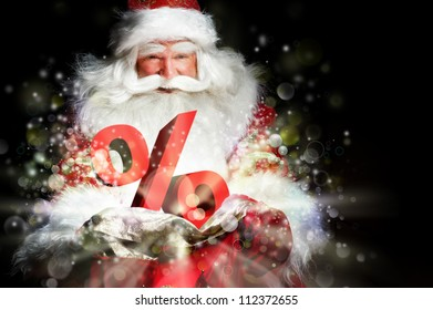 Santa Claus holding his bag and smiling. Lights and sparks are flying from the bag. Discount symbol sign in front of Santa