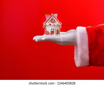 Santa Claus holding a house model with Christmas decoration on red