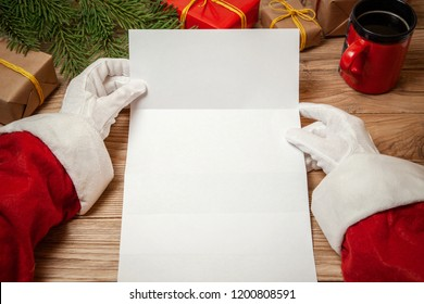 Santa Claus holding letter on wooden table with gift boxes and Christmas tree and cup of hot coffee or tea.  mockup blank