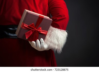 Santa Claus holding a present behind his back, close up