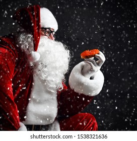 Santa Claus is holding red salmon caviar sandwich, looking at it going to eat under the snow on dark background. New year and Merry Christmas and happy holidays concept