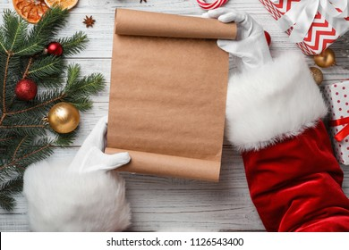 Santa Claus holding scroll and Christmas decor on wooden background, top view