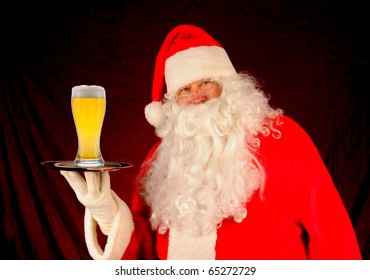 Santa Claus holding a serving tray with a large glass of beer. Horizontal format