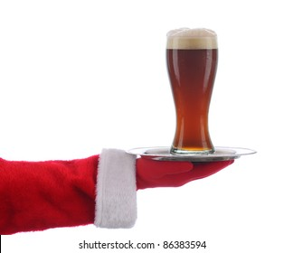 Santa Claus holding a serving tray with a glass of Dark beer over a white background.