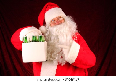 Santa Claus holding a six pack of beer bottles. Horizontal format with a maroon fabric background