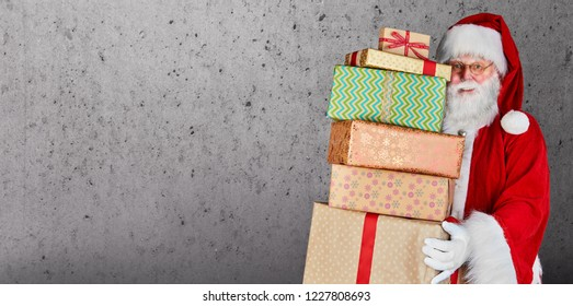 Santa Claus holding a stack of Christmas presents against a plain background with copy space.