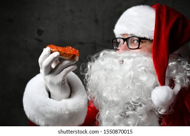 Santa Claus is holding tasty salty red salmon caviar sandwich, looking glancing at us, going to eat on dark background. New year and Merry Christmas and happy holidays concept