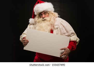 Santa Claus holding white blank sign with fun and smile standing against dark background