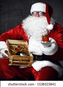 Santa Claus is holding wooden box crate with a bottle of champagne and a can of red caviar, offering us a jar of salmon caviar. New year and Merry Christmas and happy holidays concept