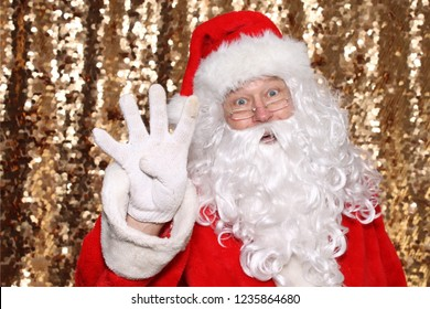 Santa Claus. Santa Claus holds Four Fingers in the air as he says there are ONLY 4  Days Until Christmas. Gold Sequin Background. Christmas Holiday Images.