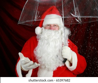 Santa Claus holds his transparent umbrella and checks for signs of snow before he goes to work on December 24th Christmas Eve