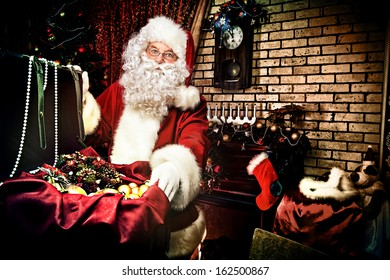 Santa Claus at home preparing for Christmas gifts.