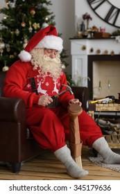 Santa Claus at Home repairing his Shoes, Preparing for Work